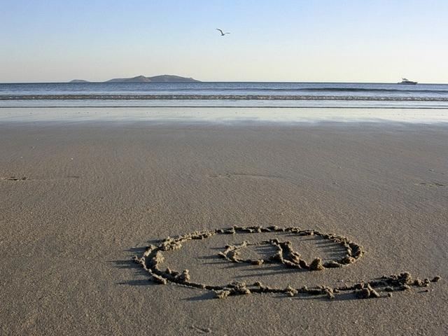 fotografie písečné pláže, v dálce moře, na písku nakreslený zavináč